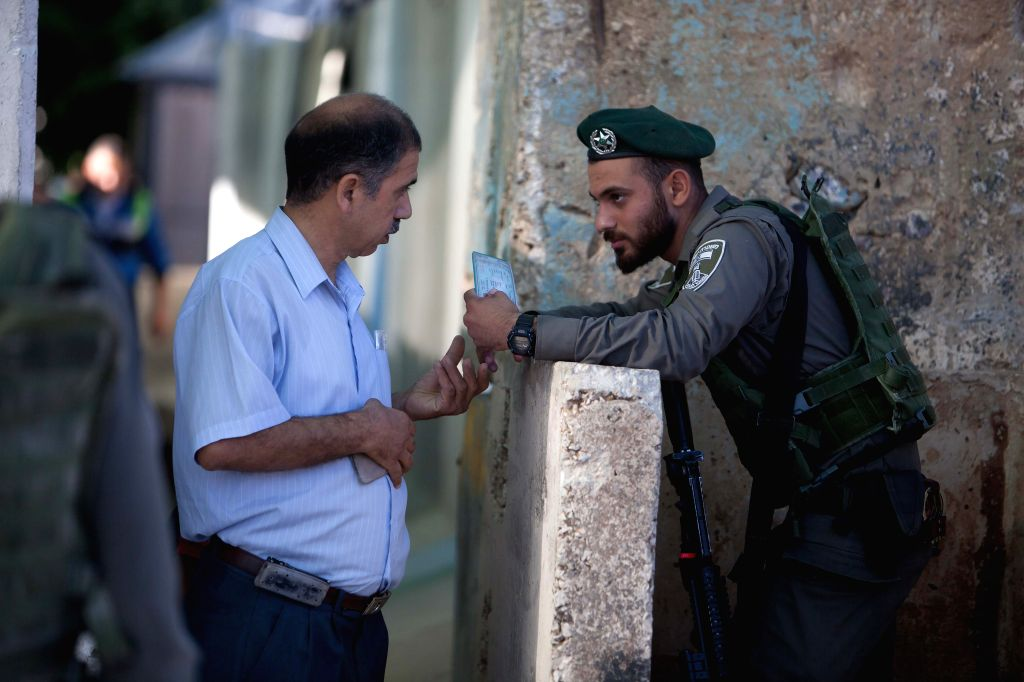 BETHLEHEM, July 1, 2016 - A Palestinian man shows his ID to an Israeli soldier as he makes his way to attend the Last Friday prayer of the holy fasting month of Ramadan in Jerusalem's al-Aqsa mosque, ...