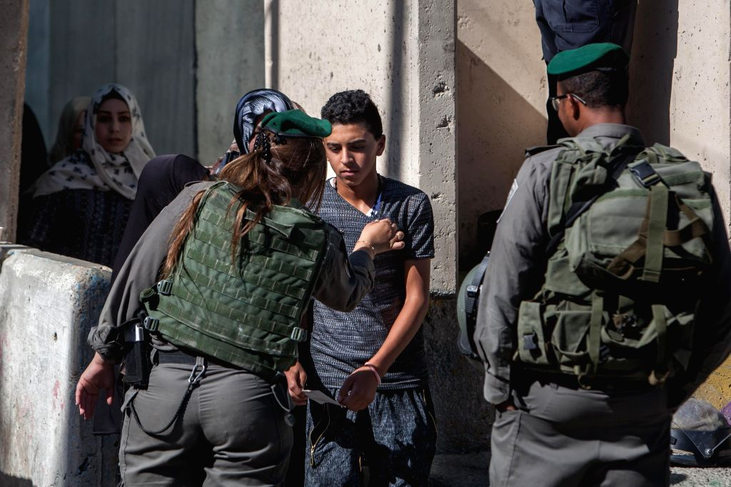 BETHLEHEM, July 1, 2016 - An Israeli security officer checks a Palestinian man as he makes his way to attend the Last Friday prayer of the holy fasting month of Ramadan in Jerusalem's al-Aqsa mosque, ...