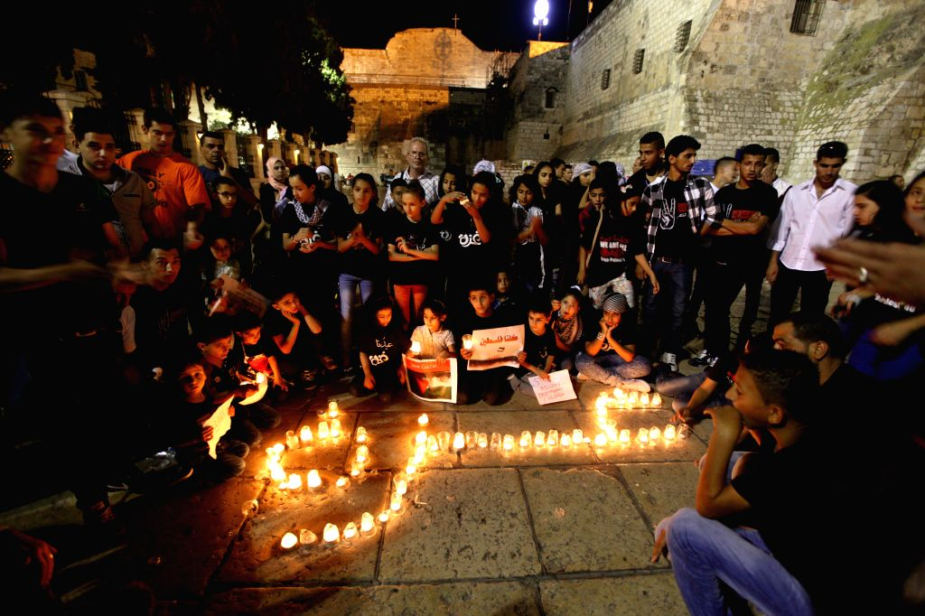 Palestinians light candles and hold posters to show support to Gaza in front of the Church of the Nativity in the West Bank city of Bethlehem on July 29, 2014. ...