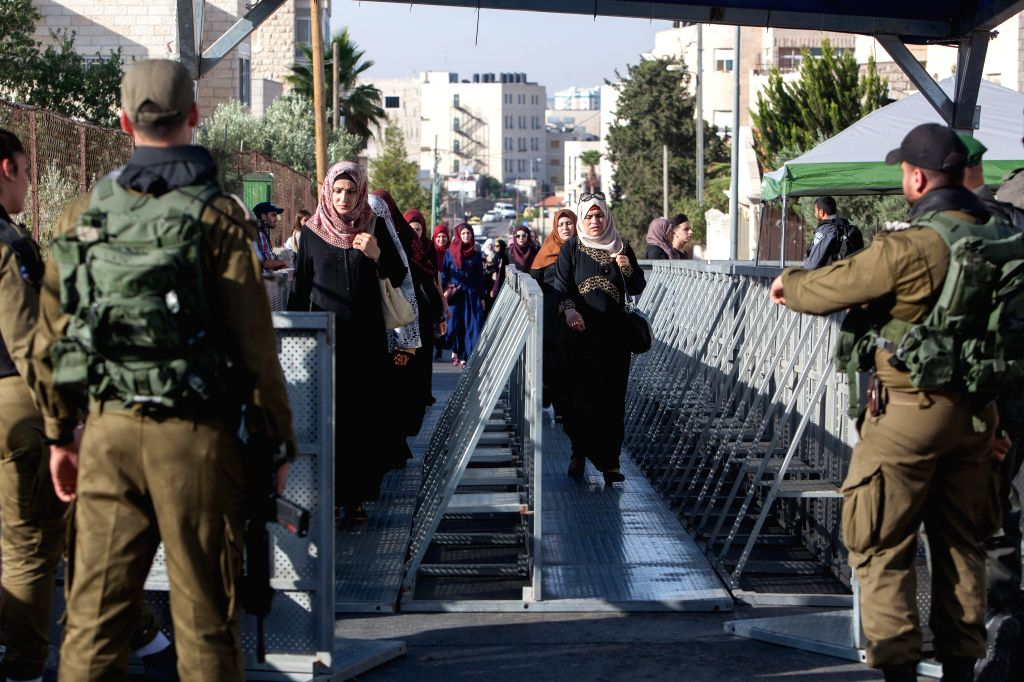 BETHLEHEM, June 8, 2018 - Palestinian women cross an Israeli checkpoint as they make their way to attend the fourth Friday prayer of the holy fasting month of Ramadan in Jerusalem's al-Aqsa mosque, ...