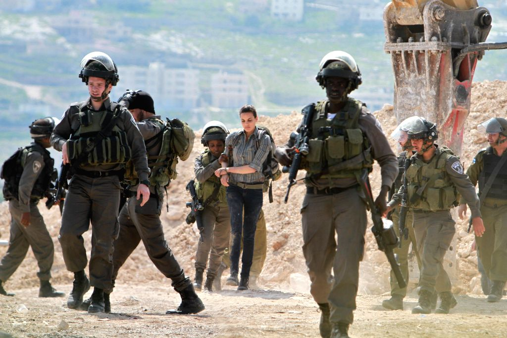 Israeli soldiers detain a foreign activist during a protest against what Palestinians say is land confiscations by Israel for Jewish settlements, near the West ...