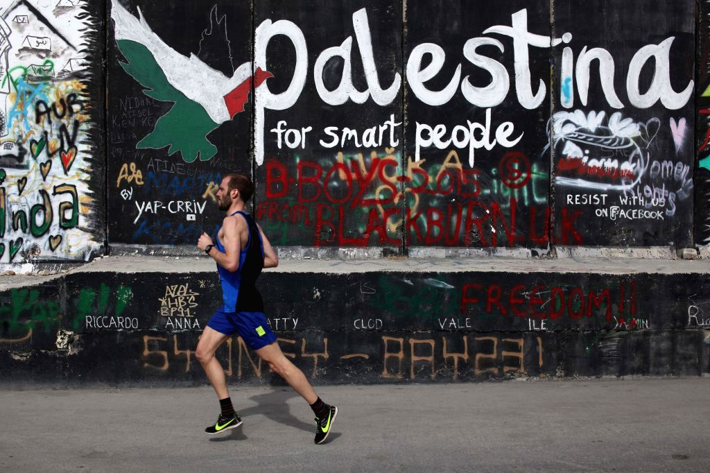 A participant runs next to the controversial Israeli barrier during the 3rd Palestine International Marathon in the West Bank city of Bethlehem on March 27, ...