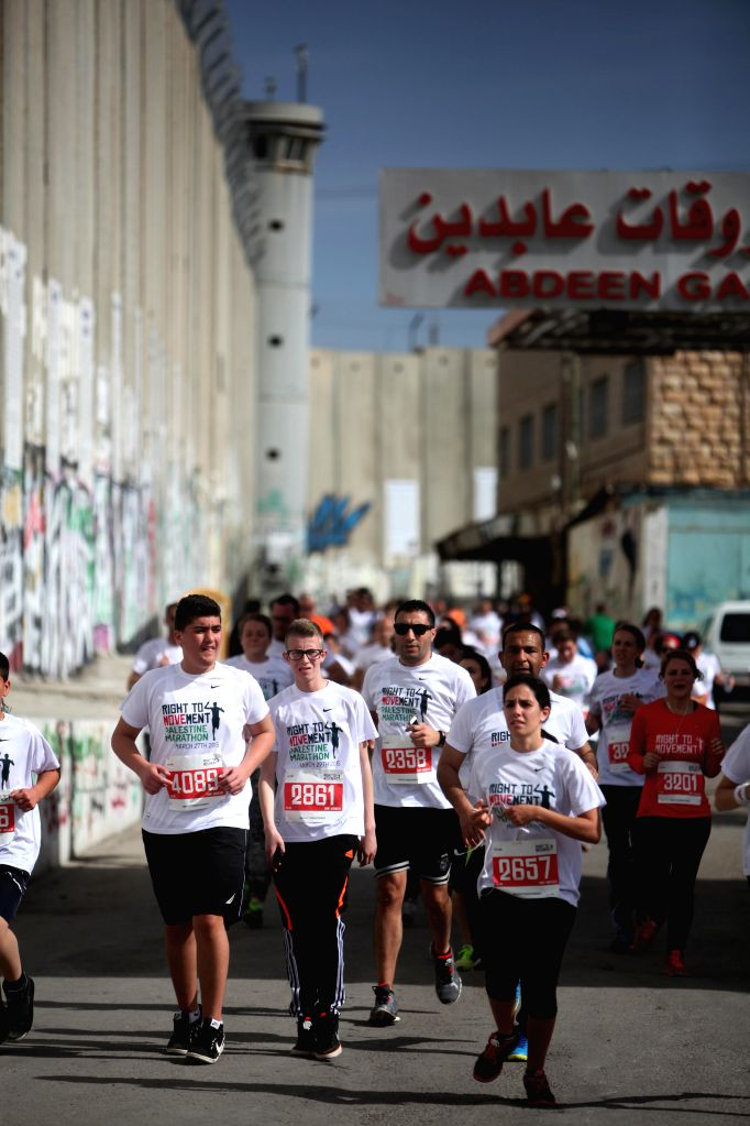 Participants run next to the controversial Israeli barrier during the 3rd Palestine International Marathon in the West Bank city of Bethlehem on March 27, 2015. ...