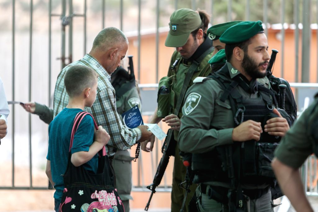 BETHLEHEM, May 25, 2018 - A Palestinian shows his ID to an Israeli security officer at an Israeli checkpoint as he makes his way to attend the second Friday prayer of the holy month of Ramadan in ...