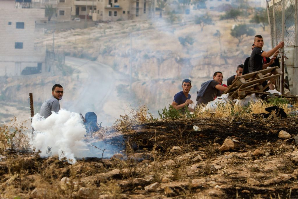 BETHLEHEM, May 25, 2018 - Palestinians, who tried to climb Israel's controversial barrier to cross into Jerusalem from the West Bank and were forbidden by Israeli security forces, run to take cover ...