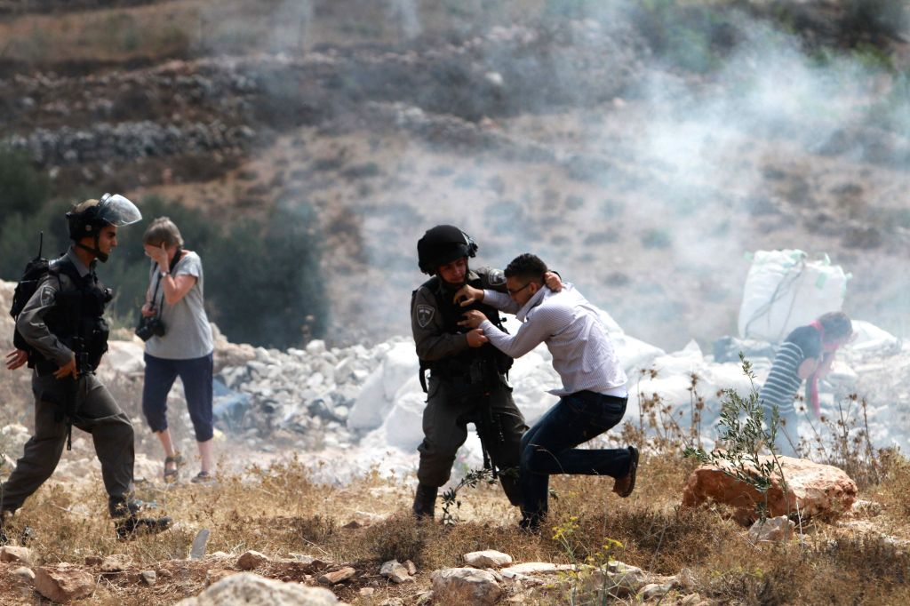 An Israeli soldier clashes with a Palestinian youth during a protest in the West Bank village of Wadi Fukin near city of Bethlehem on Sept. 5, 2014. On Sunday, ...