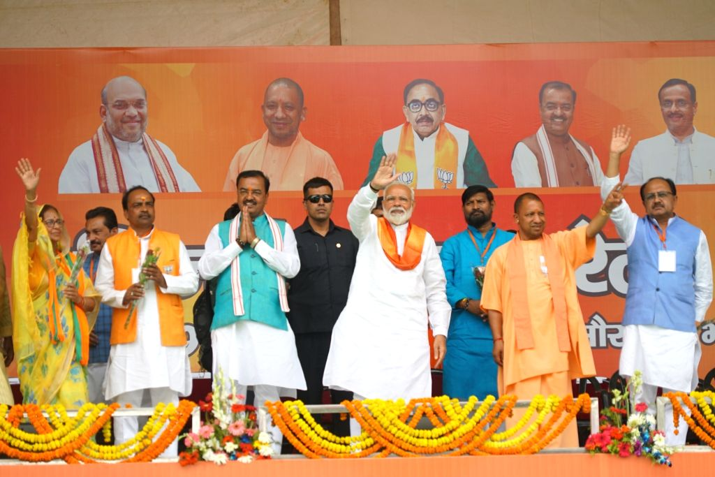 Bhadohi: Prime Minister Narendra Modi accompanied by Uttar Pradesh Chief Minister Yogi Adityanath and Deputy Chief Minister Keshav Prasad Maurya, waves to crowd during his public rally, in Bhadohi, Uttar Pradesh, on May 5, 2019. (Photo: IANS) * * - Narendra Modi