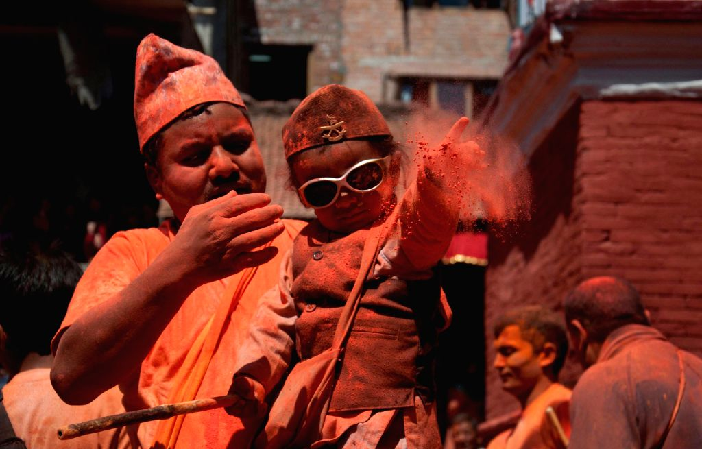 A child throws vermillion powder during the Sindur Jatra festival at Thimi, Bhaktapur, Nepal, April 15, 2014. Sindur Jatra, or Vermilion Powder Festival, was ...