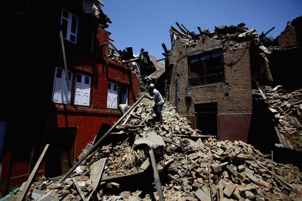 A man collects his belongings from houses damaged by earthquake in Bhaktapur, Nepal, April 27, 2015. Death toll climbed to 3,815 following a massive ...