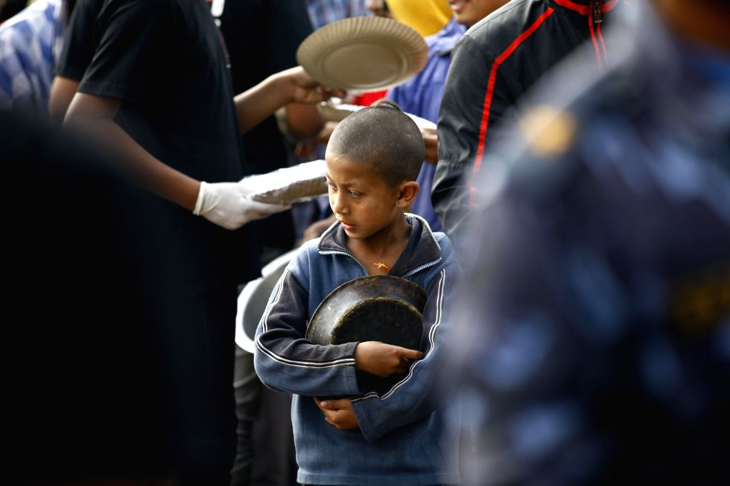 A displaced child queues for food relief in Bhaktapur, Nepal, April 29, 2015. The 7.9-magnitude quake hit Nepal at midday on Saturday. (Xinhua/Pratap Thapa) ...