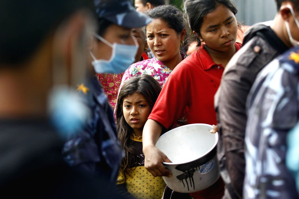 Displaced people queue for food relief in Bhaktapur, Nepal, April 29, 2015. The 7.9-magnitude quake hit Nepal at midday on Saturday. (Xinhua/Pratap Thapa) ...