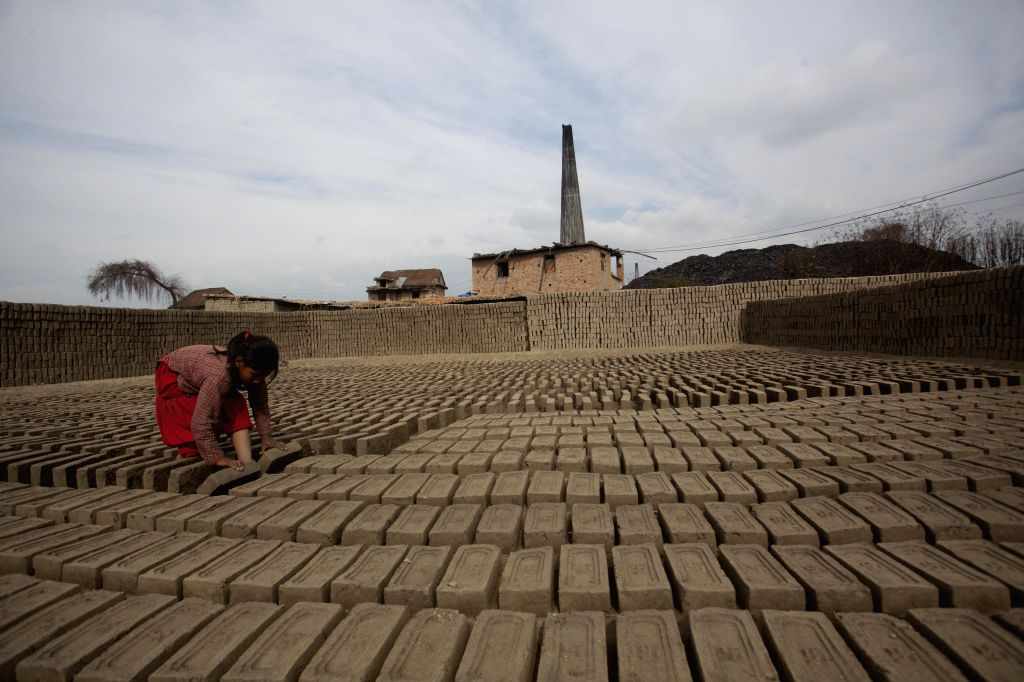 A girl works at a brick factory in Bhaktapur, Nepal, Jan. 13, 2015.