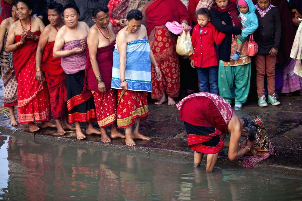 Nepalese Hindu women worship at the Hanumante River during the month-long Madhav Narayan festival at Bhaktapur, Nepal, Jan. 17, 2015.