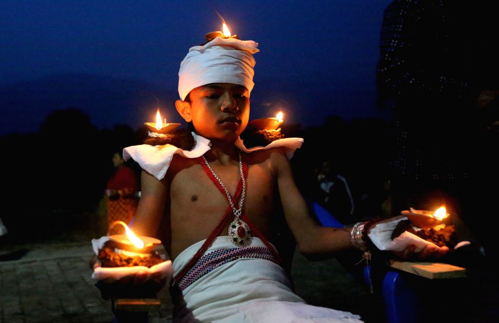 BHAKTAPUR, Oct. 8, 2019 - A boy stays with oil lamps on his head and hands while offering prayers to Goddess Durga on Bijaya Dashami, the tenth day of the Dashain Festival which celebrates the ...