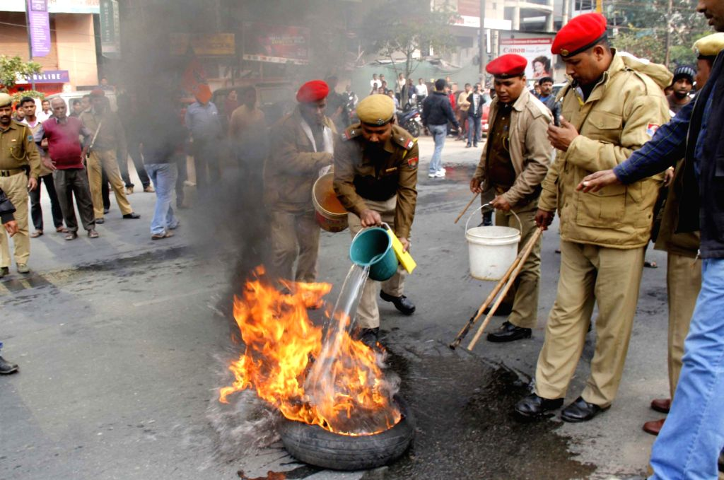 Bharatiya Janata Party (BJP) workers burn a tyre during 12-hour Assam Bandh called by the BJP to protest against the tabling of Constitutional Amendment Bill in Rajya Sabha, in Guwahati on Dec.20, ...