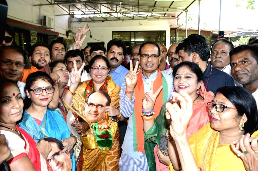 Bhopal: BJP leader Shivraj Singh Chouhan and his wife Sadhna Singh show victory sign as they celebrate with party workers after the counting trends for the 2019 Lok Sabha elections show that the party appeared set to retain power as its candidates le - Shivraj Singh Chouhan and Sadhna Singh