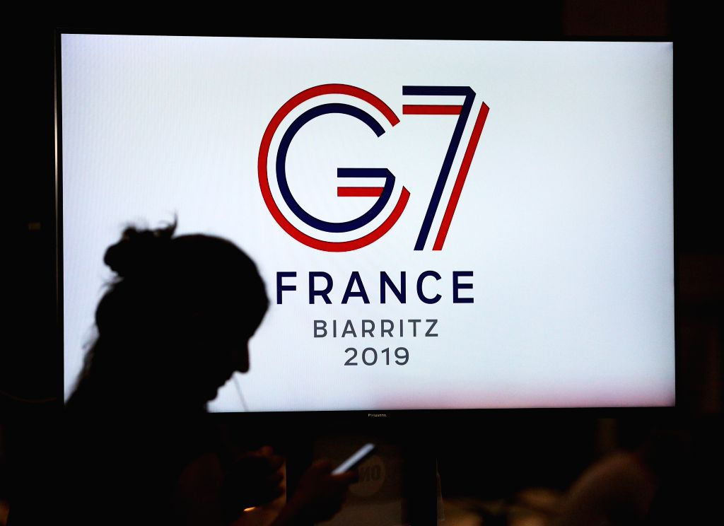 BIARRITZ, Aug. 25, 2019 - A journalist is silhouetted on a TV screen at the G7 summit press center in Biarritz, France, Aug. 25, 2019. ers from the world's seven most industrialized countries ...