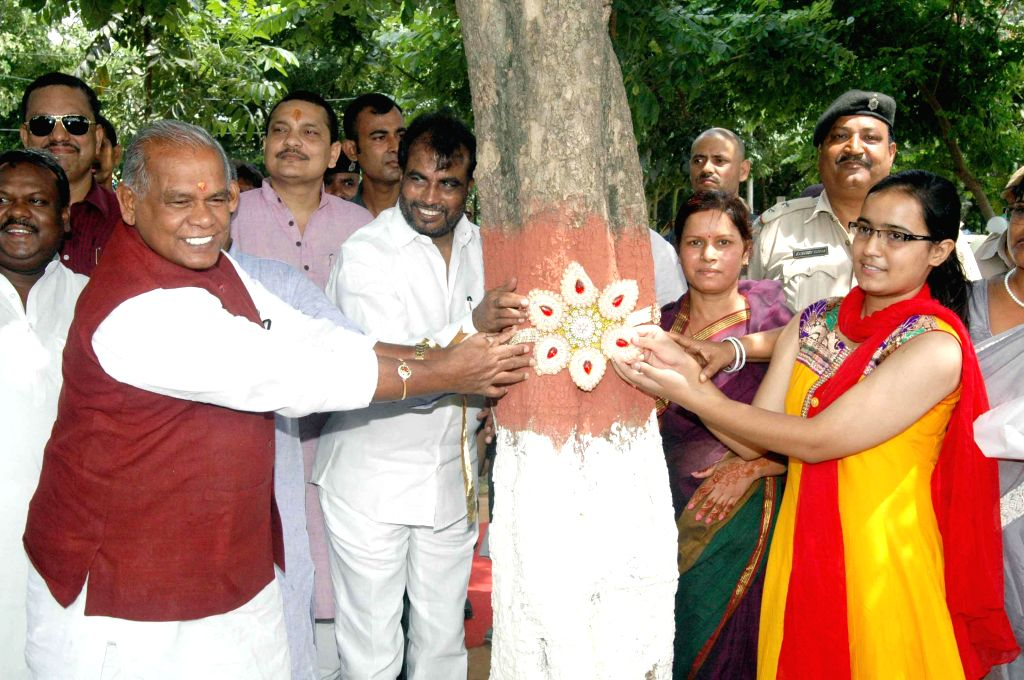 Bihar Chief Minister Jitan Ram Majhi ties a rakhi to a tree on Raksha Bandhan in Patna on Aug 10, 2014. - Jitan Ram Majhi
