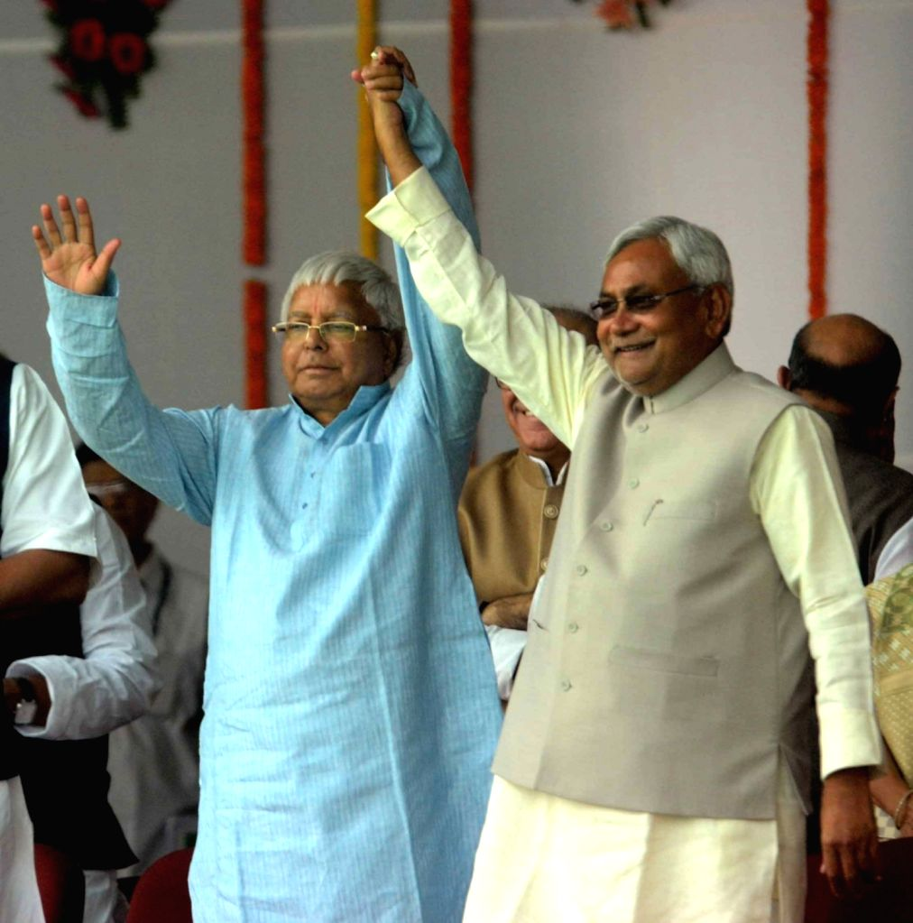 Bihar Chief Minister Nitish Kumar and RJD supremo Lalu Prasad Yadav embrace each other during the swearing-in ceremony of the new JD-U-RJD-Congress coalition government in Patna, on Nov 20, ... - Nitish Kumar and Lalu Prasad Yadav