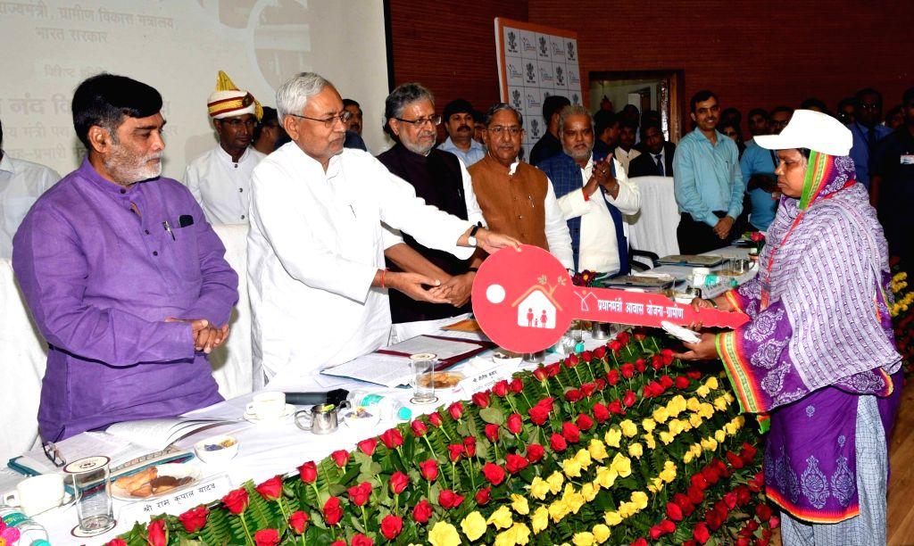 Bihar Chief Minister Nitish Kumar and Union MoS Rural Development Ram Kripal Yadav hands over keys of houses to beneficiaries of Pradhan Mantri Awas Yojana during a programme, in Patna, on ... - Nitish Kumar