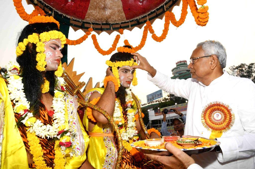 Bihar Chief Minister Nitish Kumar applies 'tilak' on the foreheads of artistes dressed up as Lord Ram and Laxman at 'Ramleela Mahotsav' during Dussehra celebrations in Patna, on Oct 8, 2019. - Nitish Kumar