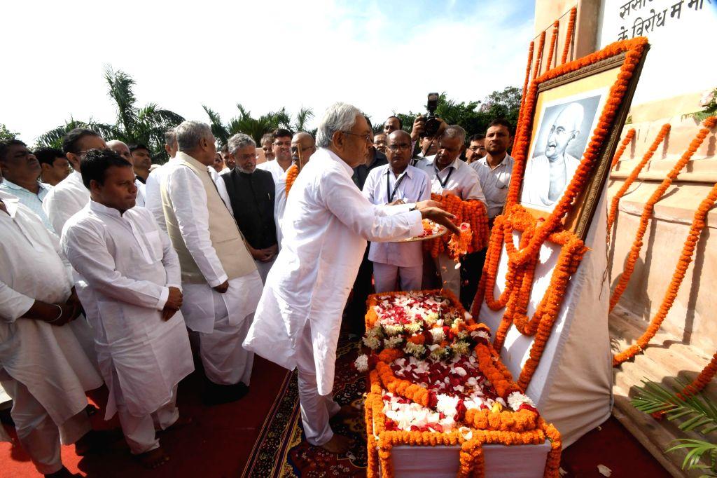 Bihar Chief Minister Nitish Kumar pays tribute to the portrait of Mahatma Gandhi's on his 150th birth anniversary in Patna on Oct 2, 2019. Bihar Governor Phagu Chauhan and Bihar Deputy Chief ... - Nitish Kumar, Phagu Chauhan and Sushil Kumar Modi