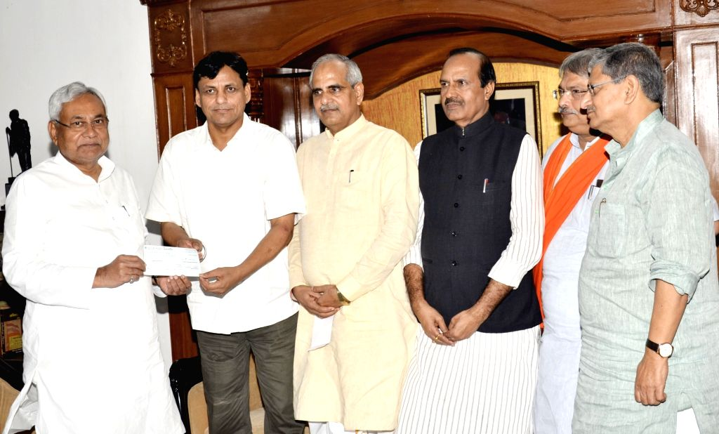 Bihar Chief Minister Nitish Kumar receives a cheque from state BJP President Nityanand Rai as donations to Chief Minister's Relief Fund to help flood victims of Bihar, in Patna on Aug 16, 2017. - Nitish Kumar and Nityanand Rai