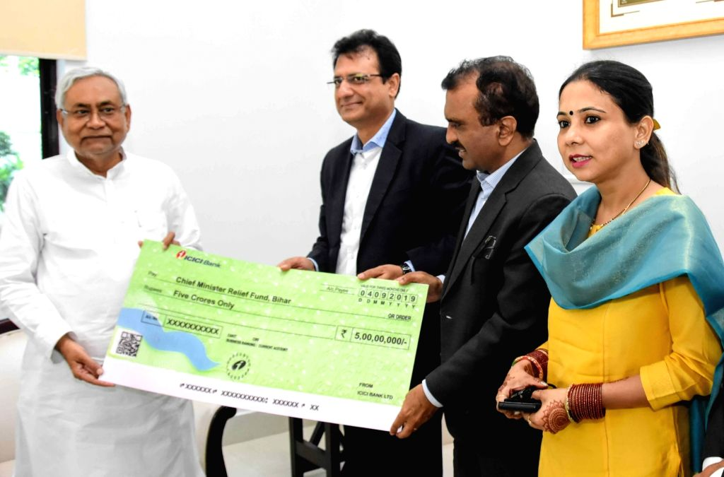 Bihar Chief Minister Nitish Kumar receives a cheque of Rs 5 Crore from the officials of ICICI Bank as a contribution towards the Chief Minister's Relief Fund, in Patna on Sep 4, 2019. - Nitish Kumar