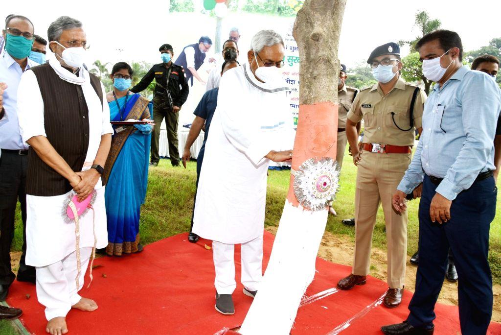 Bihar Chief Minister Nitish Kumar ties a rakhi to a tree on the occasion of Raksha Bandhan in Patna on Aug 3, 2020. - Nitish Kumar