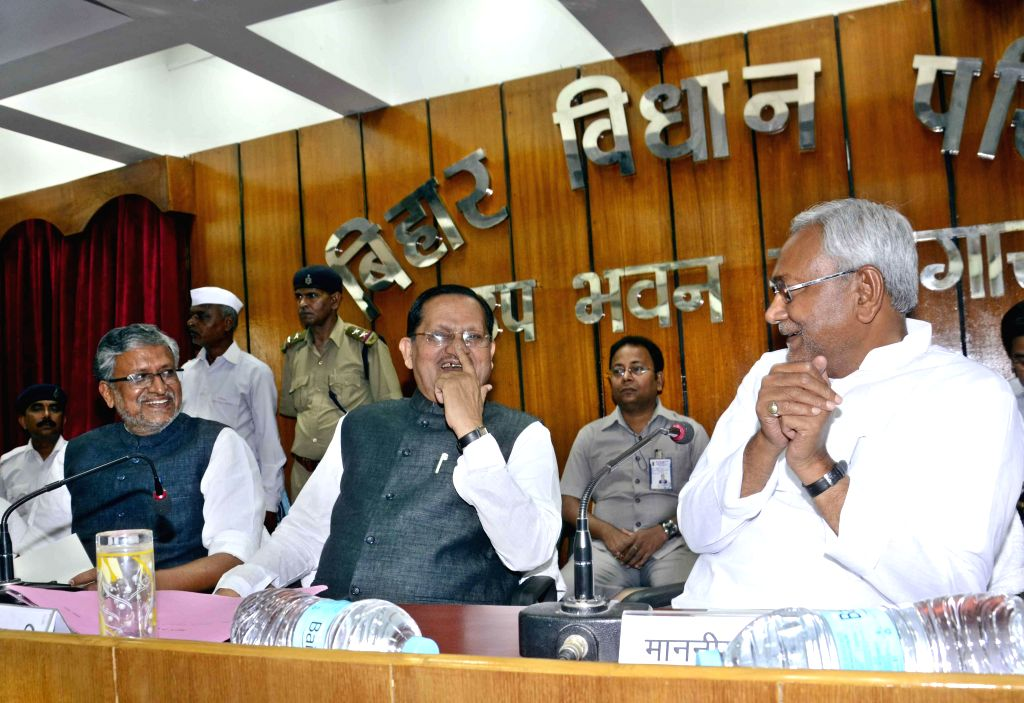 Bihar Chief Minister Nitish Kumar, with BJP leader Sushil Kumar Modi and newly appointed legislative council chairman Awadhesh Narayan Singh during Singh's oath taking ceremony in Patna on May 13, ... - Nitish Kumar and Sushil Kumar Modi