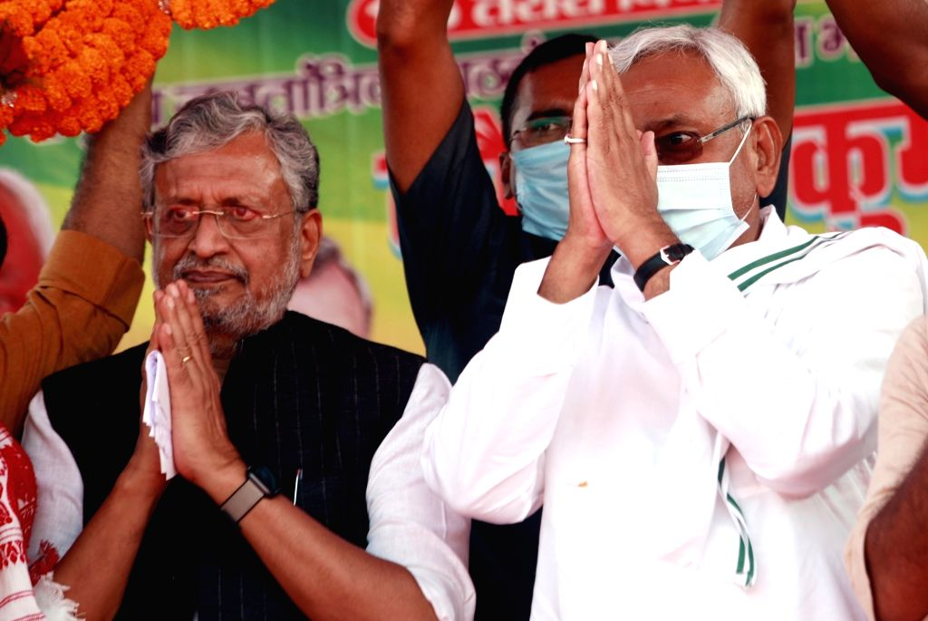 Bihar Chief Minister Nitish Kumar with Deputy CM Susheel Kumar Modi being garland by supporters during an election meeting, ahead of Bihar Assembly elections at Trari constituency in Bhojpur ... - Nitish Kumar and Susheel Kumar Modi