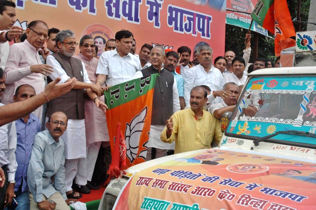 Bihar Deputy Chief Minister Sushil Kumar Modi flags off relief material for the flood victims at BJP office in Patna on Aug 20, 2017. - Sushil Kumar Modi