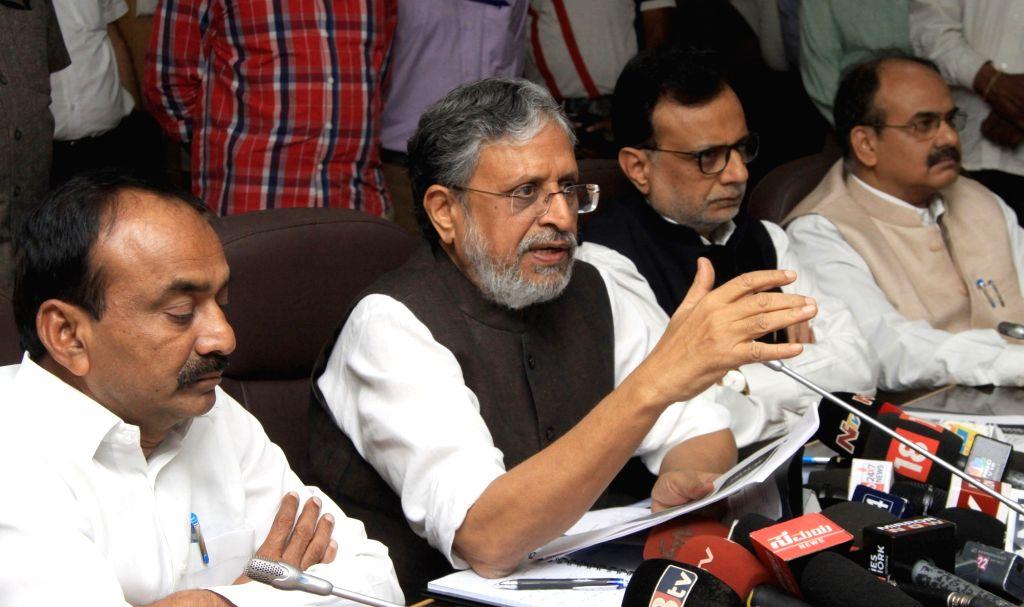 Bihar Deputy Chief Minister Sushil Kumar Modi, Union Finance Secretary Hasmukh Adhia and Telangana Finance Minister Etela Rajender at a press conference during a meeting at Vidhan Soudha ... - Sushil Kumar Modi