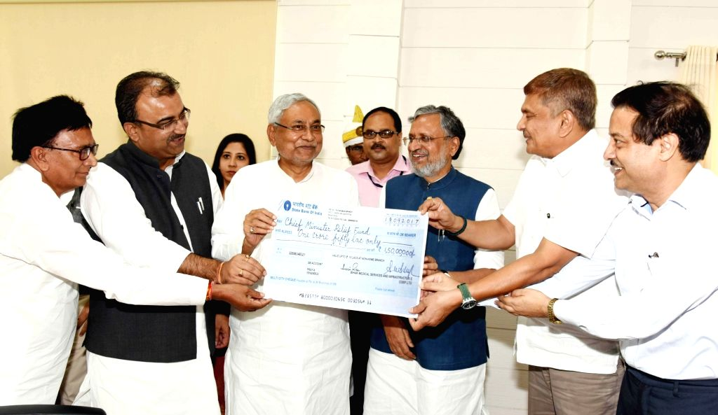 Bihar Health Minister Mangal Pandey presents a cheque to Bihar Chief Minister Nitish Kumar as a contribution to the Chief Minister's Relief Fund in Patna on Sept 18, 2017. Also seen Bihar ... - Mangal Pandey, Nitish Kumar and Sushil Kumar Modi