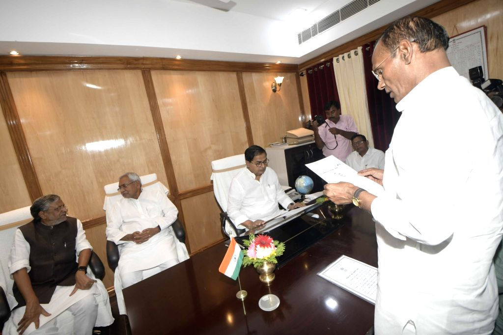 Bihar Legislative Council Chairman Mohammad Haroon Rashid??? administers the oath of office to the newly elected BJP MLC Radha Mohan Sharma, in Patna on June 4, 2019. Also seen Bihar Chief ... - Nitish Kumar, Radha Mohan Sharma and Sushil Kumar Modi