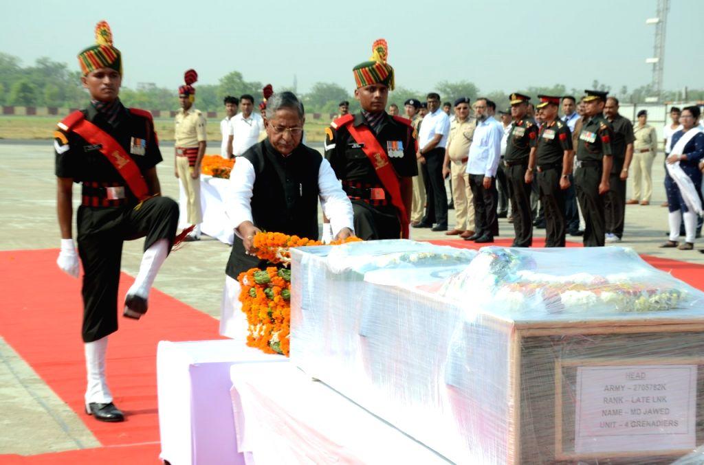 Bihar Minister Nand Kishore Yadav lays wreath on the mortal remains of soldier Lance Naik Mohammad Jawed, at the Jay Prakash Narayan International Airport in Patna on June 12, 2019. Jawed was ... - Nand Kishore Yadav