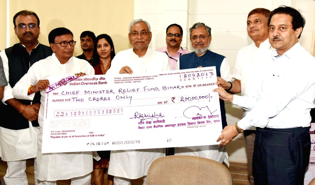 Bihar's Public health Minister Krishna Nandan Prasad Verma presents a cheque to Bihar Chief Minister Nitish Kumar as a contribution to the Chief Minister's Relief Fund in Patna on Sept 18, ... - Krishna Nandan Prasad Verma, Nitish Kumar and Sushil Kumar Modi