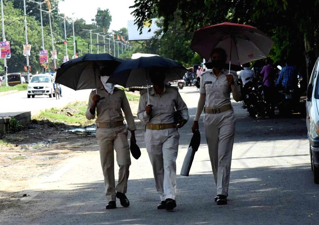 Bihar women police personnel use umbrellas to shield themselves from the sun as they discharge their duties on a hot and humid day, in Patna on July 5, 2020.