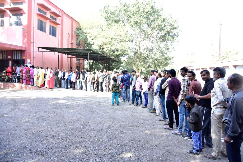 Bikaner: Voters wait in a queue at a polling station to cast their votes for Rajasthan Assembly elections, in Bikaner on Dec 7, 2018. (Photo: IANS)