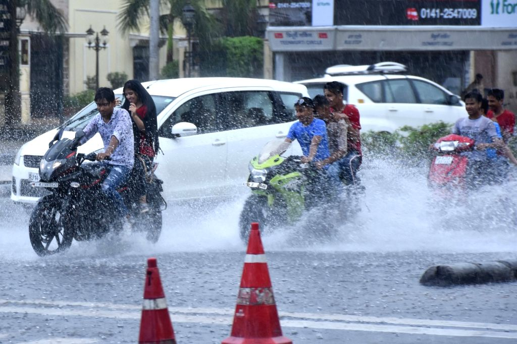 Bikers splashing through the water as they speeds on a waterlogged road of Jaipur on July 28, 2019.