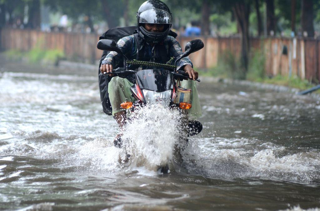 Bikers struggle through water-logged streets of Kolkata, on July 3, 2016.