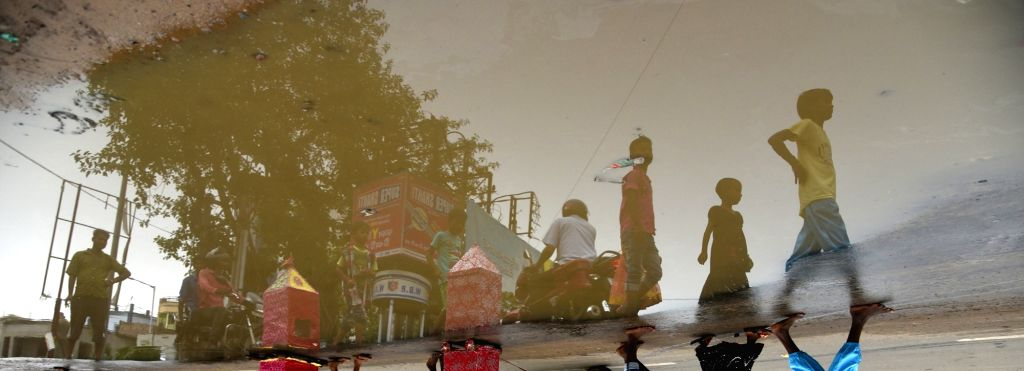 Birbhum: A reflection of children participating in the Bahuda Yatra-the home coming of Lord Jagannath, Lord Balabhadra, Lord Sudarshan and Devi Subhadra from Gundicha Temple to Srimandir; seen in rain water accumulated at a street-side in Bolpur of W - Indrajit Roy