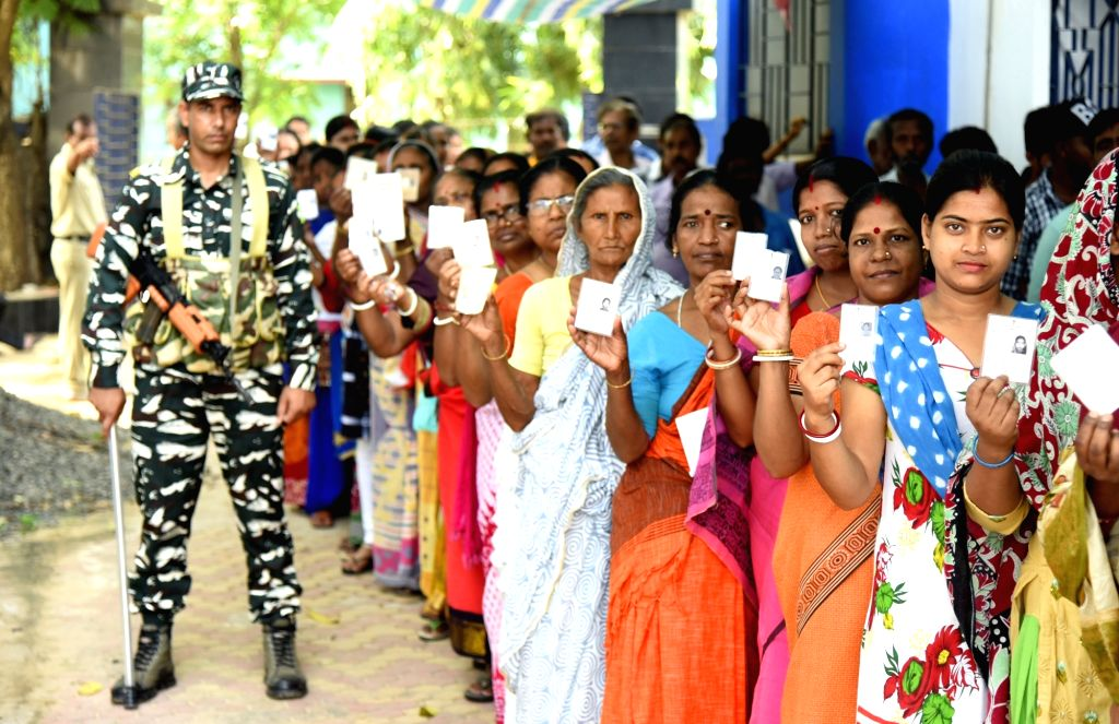Birbhum: A security personnel stands guard as women queue up to cast their votes for the fourth phase of 2019 Lok Sabha elections at a polling station at Bolpur in West Bengal's Birbhum, on April 29, 2019. (Photo: Indrajit Roy/IANS) - Indrajit Roy
