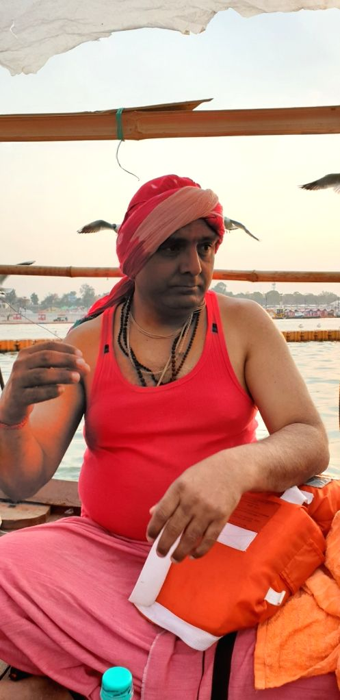 Birds spying on your ears...  A man sitting on the banks of the Ganga river in Prayagraj.