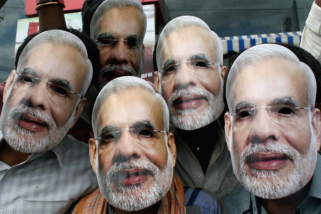 BJP (Bharatiya Janata Party) Prime Ministerial candidate and Gujarat Chief Minister Narendra Modi supporters wearing `Narendra Modi masks at Palace Grounds` in Bangalore on Nov.17, 2013. (Photo: IANS) - Narendra Modi