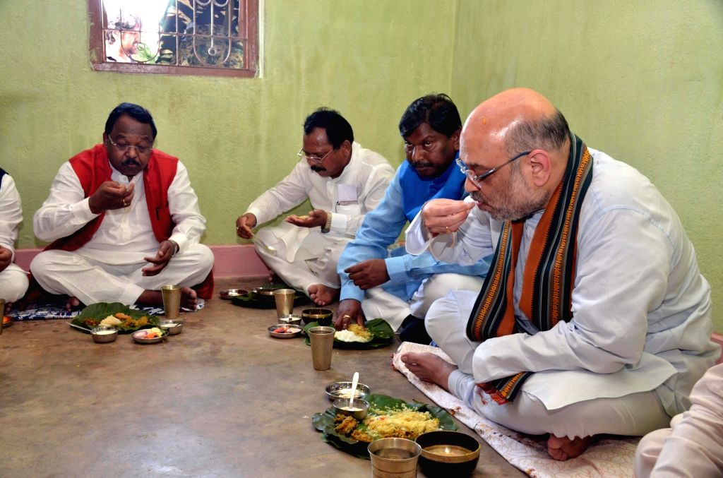 BJP chief Amit Shah and former Jharkhand Chief Minister Arjun Munda at a tribal party worker's residence in Ranchi on Sept 16, 2017. - Arjun Munda and Amit Shah