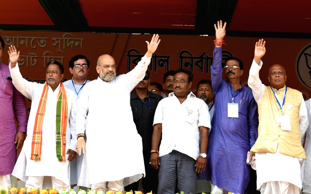 BJP chief Amit Shah and party leader Mukul Roy wave at supporters during a public rally at Rajarhat in Kolkata on May 13, 2019. - Amit Shah and Mukul Roy