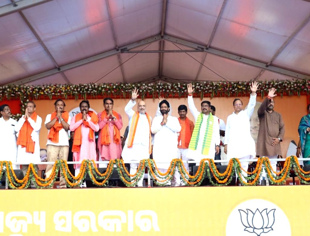 BJP chief Amit Shah and Union Minister Dharmendra Pradhan wave at supporters during a public rally in Odisha's Jajpur, on April 27, 2019. - Dharmendra Pradhan and Amit Shah