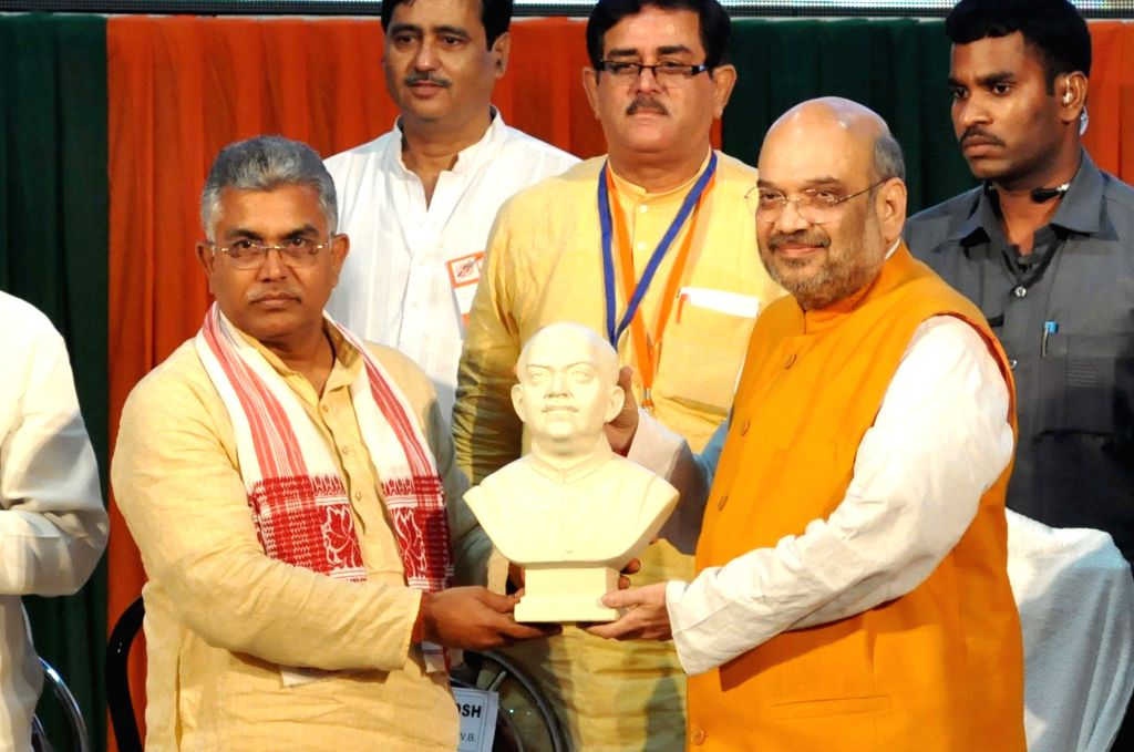 BJP chief Amit Shah being felicitated by party's West Bengal chief Dilip Ghosh during a party program in Kolkata on April 26, 2017. - Amit Shah and Dilip Ghosh