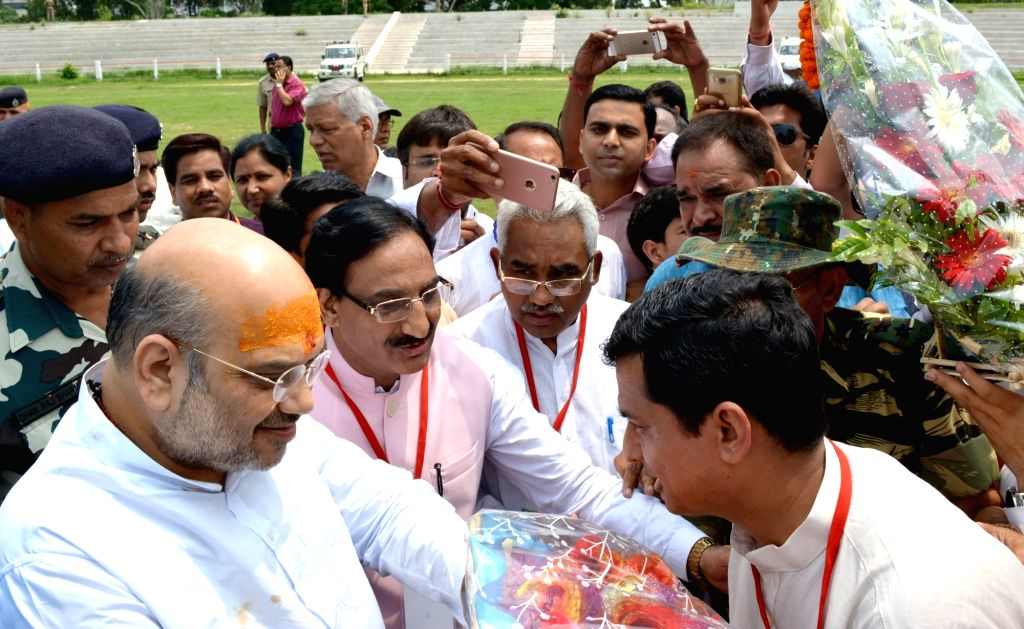 BJP chief Amit Shah being greeted by BJP MP Ramesh Pokhriyal Nishank on his arrival in Haridwar on June 25, 2016. - Amit Shah